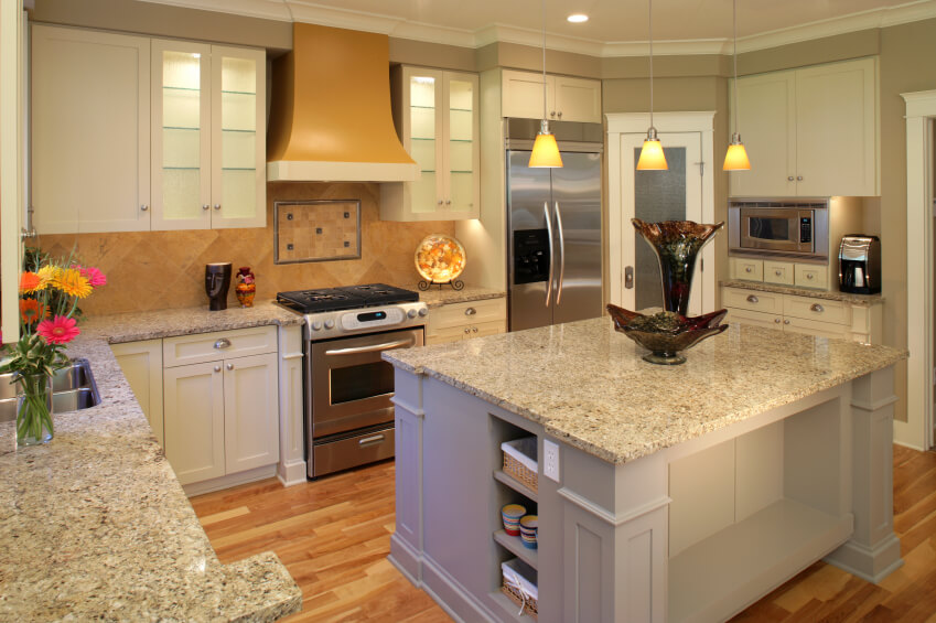 Light granite countertops highlight the color palette of this kitchen ...