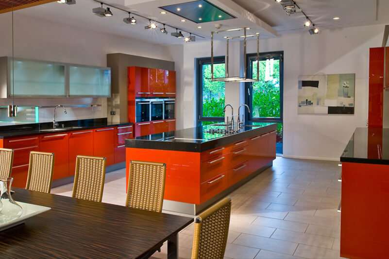 Here's another high contrast kitchen, with deep red cabinetry and large kitchen island, bracketing rich black countertops and white walls over beige large format tile flooring. Slim stainless steel hardware adorns the cabinetry, pairing well with upper level smoked glass cupboard doors.