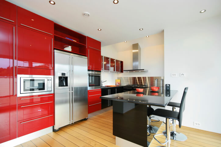 This bright open-plan kitchen features a large black island with dining space for two, defining the space. Glossy red cabinetry from floor to ceiling wraps the stainless steel appliances, while a matching steel backsplash adds extra sparkle to the room.
