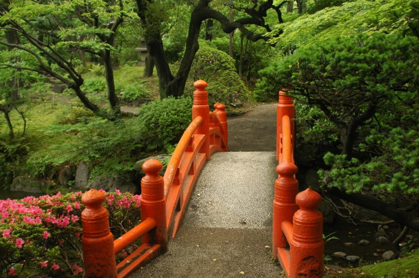 The carved wooden railings along this bridge are painted a bold Chinese red that looks almost orange in the failing light.