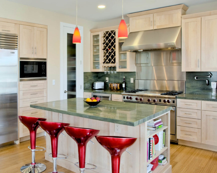 Here's an ultra-modern kitchen flush with bold, smooth textures. Green marble countertops and backsplashes, along with a set of cherry red bar stools, add a burst of color to the white space, over light hued hardwood flooring.