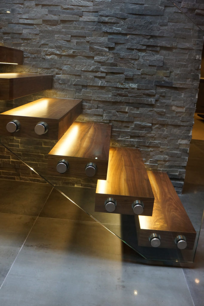 Here's a close view of the staircase, with rich wood tones lit via embedded lighting strips. The all-glass framing helps keep the structure unobtrusive within the open design.