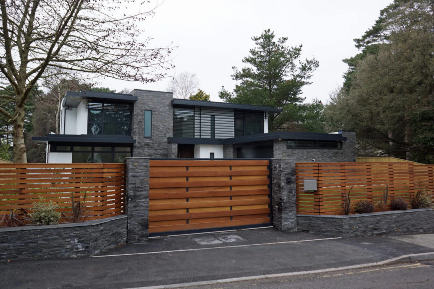 A rich wood panel and stone gate surrounds the home, enhancing privacy for the residents.