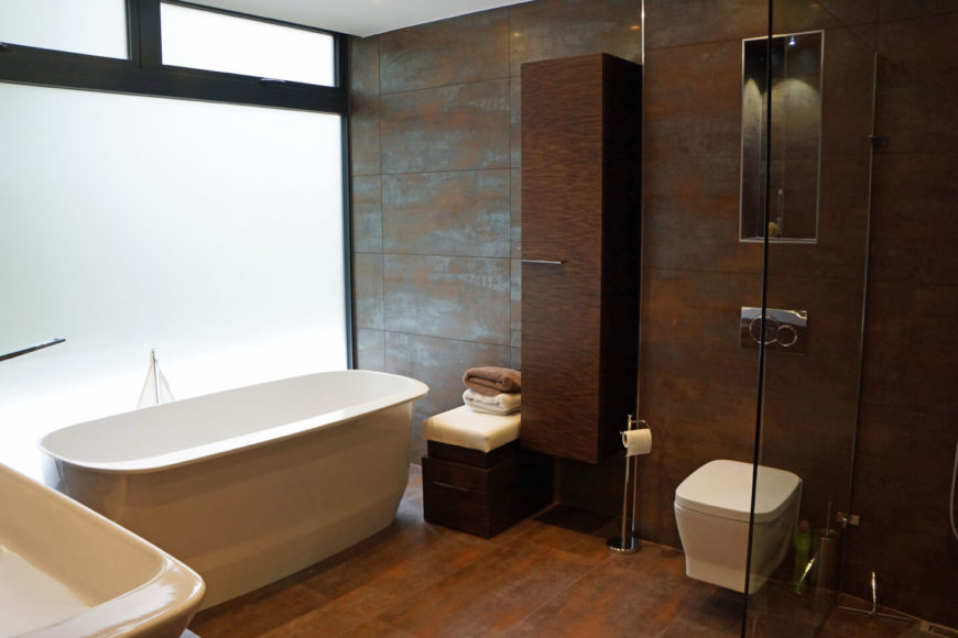 The bathroom is awash in copper tones, adding high contrast between the white soaking tub, vanity, and plumbing, and the walls and flooring. Open-design shower stands behind glass enclosure at right.