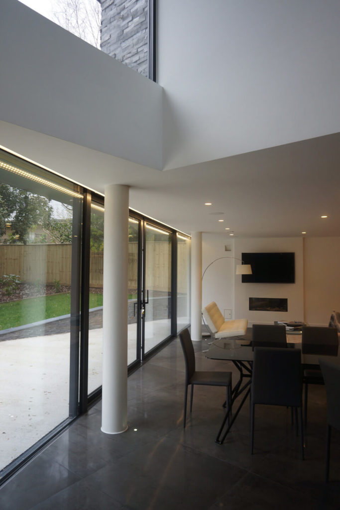In the open-plan space, the dining table stands in black, with white contemporary seating defining the living room space behind. Full height glass wrapping the exterior provides extraordinary views and blends the indoor and outdoor spaces.