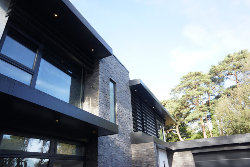Gazing upward, we see the expanses of full height glazing across the exterior, bracketed above and below by dark tinted metal structural elements.