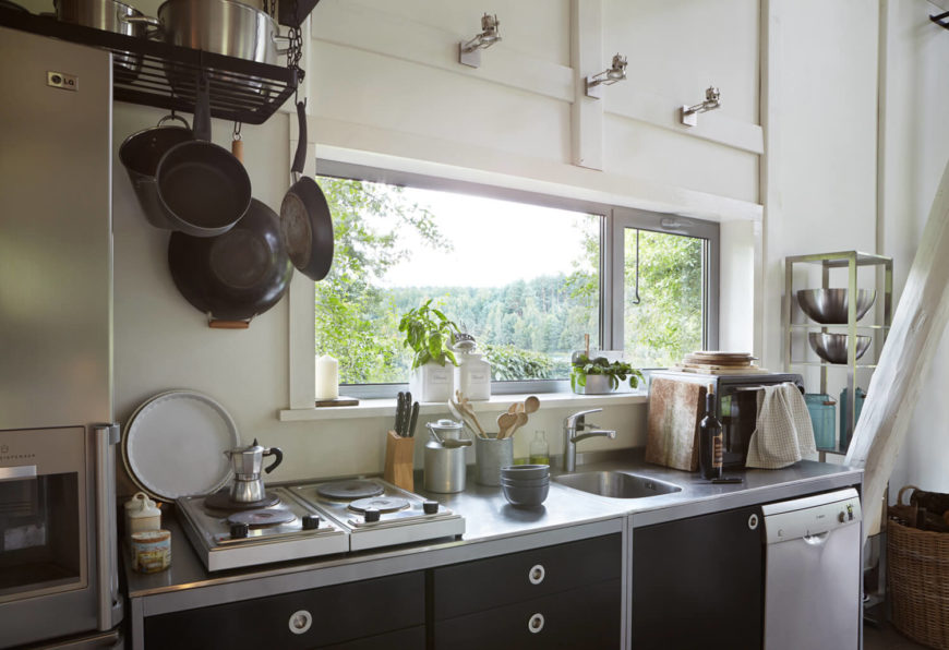 With hanging storage and free standing metal shelving to the right, the cozy kitchen makes the most of its corner of the room.