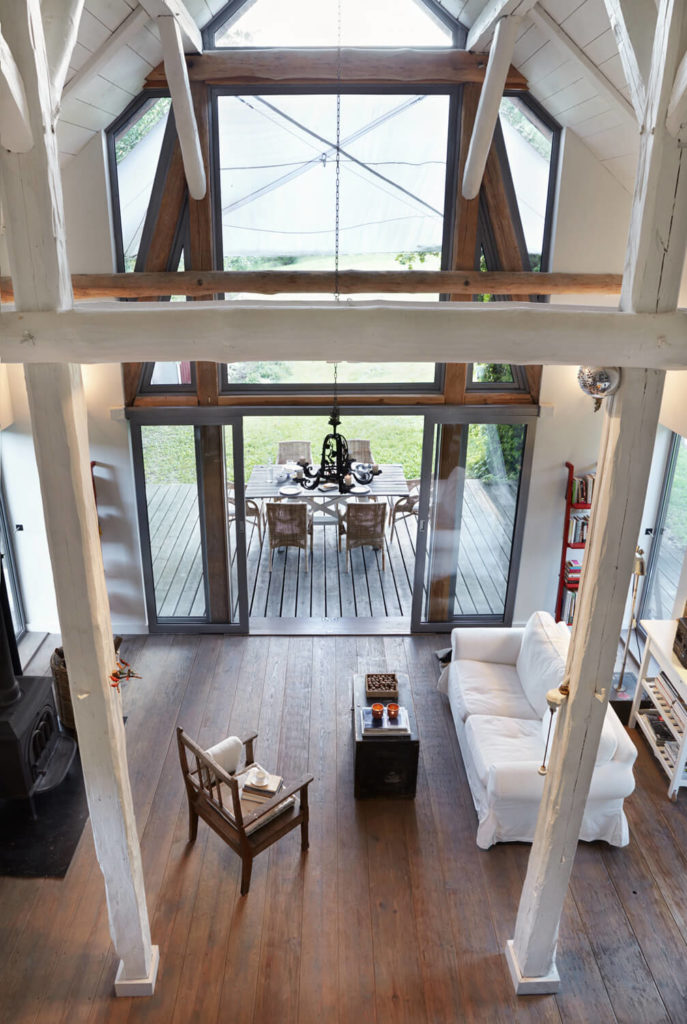 Viewed from above, the living room is defined by the twin white pillars at center. White sofa and block-shape coffee table comprise most of the furniture, below exposed natural beams framing the entry windows.