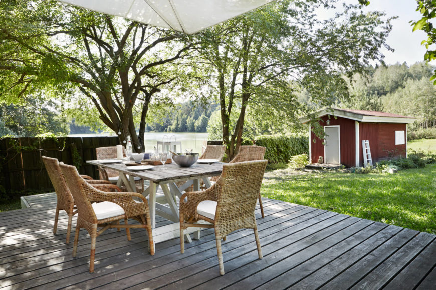 The dining set on the terrace features a natural wood table and set of wicker chairs, with shade provided by nearby trees.