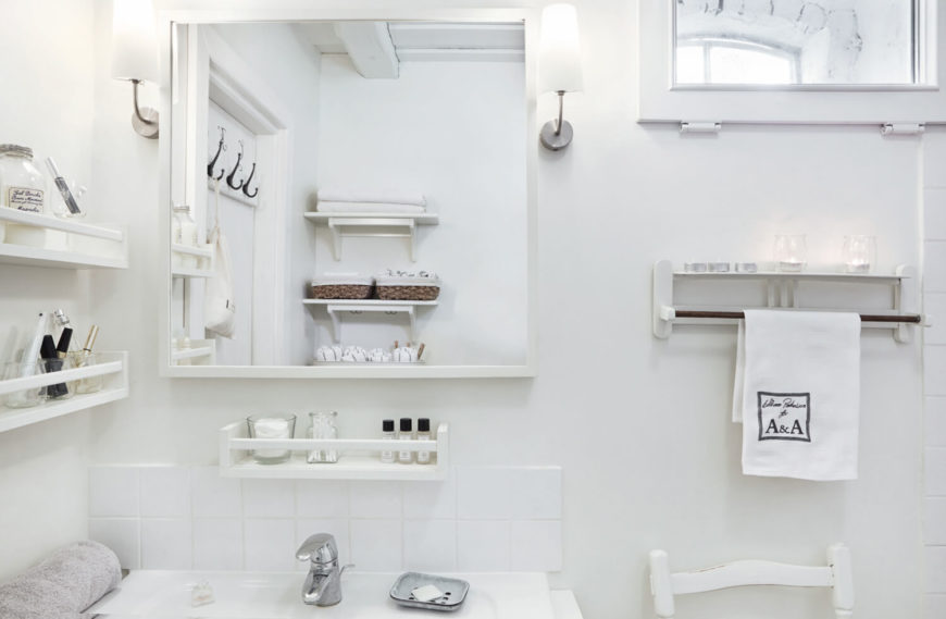 The white-on-white theme allows for a surprising amount of detail, with wall mounted shelving appearing throughout the bathroom.