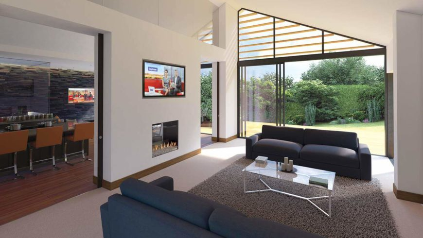 The more formal living room is separated from the open-concept room to the left by a small wall that contains a glass-enclosed fireplace. The low, cream carpeting is covered by a light gray plush rug. Sliding glass doors lead out to the backyard.