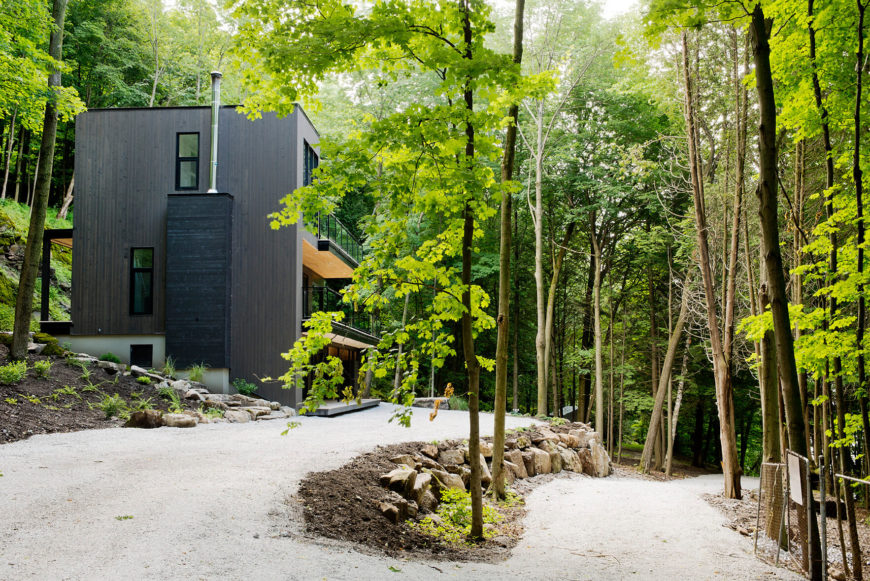 Moving back a ways, we see the surrounding light gravel and stone stairway wrapping the home, helping define its place within the forest.