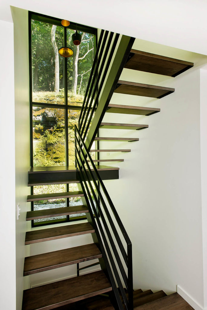 The staircase is backed by a vertical arrangement of windows running the full height of the structure.