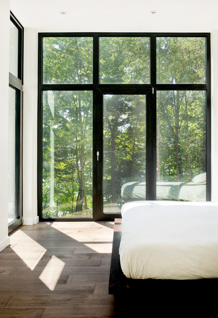 On the top floor, the master bedroom enjoys expansive views of the surrounding forest and lake beyond.