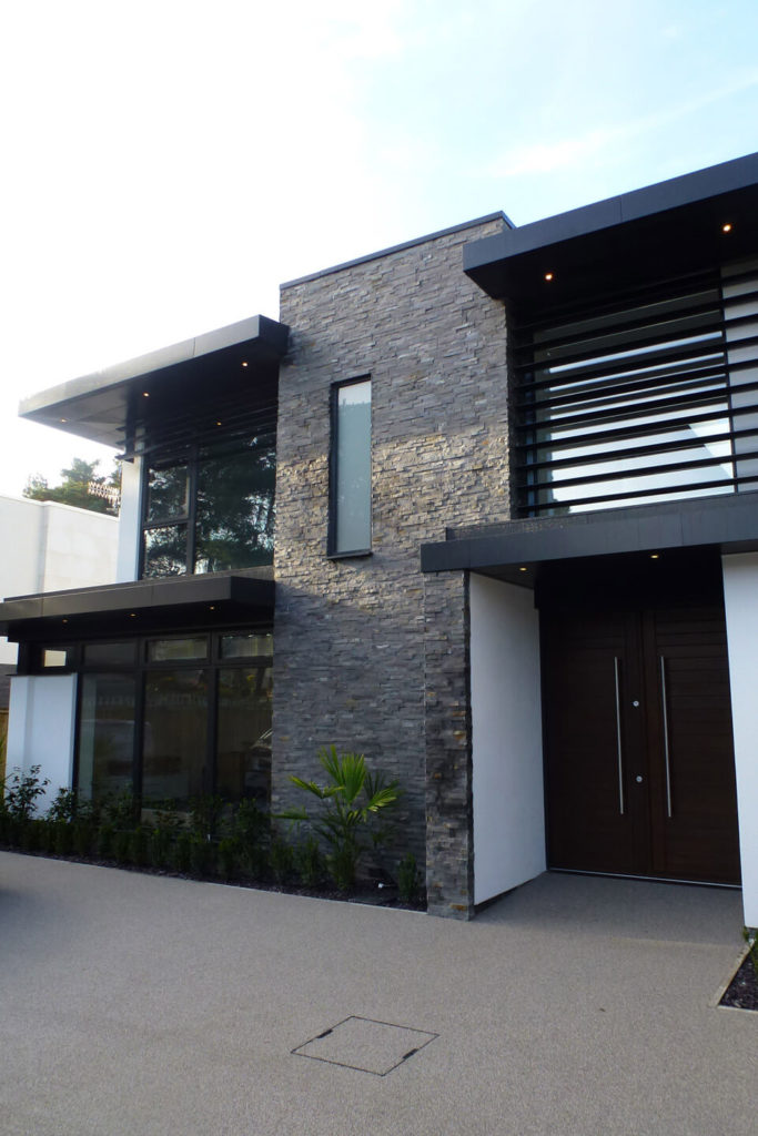 The central stone brick portion bisects the structure, flanked by expanses of glass that afford spectacular views from within the home. A slim garden hugs the low exterior wall.