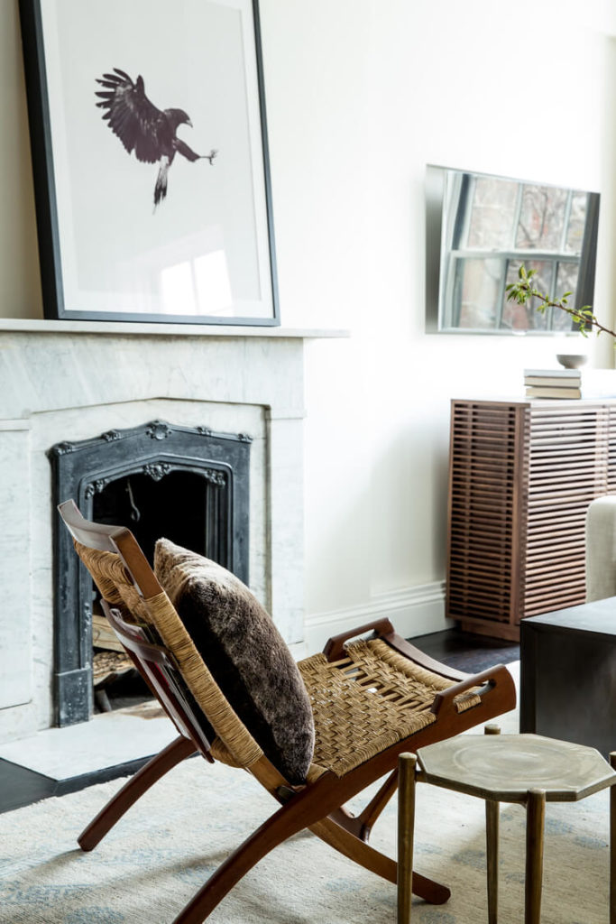 The open-plan living room includes interesting furniture pieces, like this folding wood and wicker chair, and the slatted wood media cabinet at right.