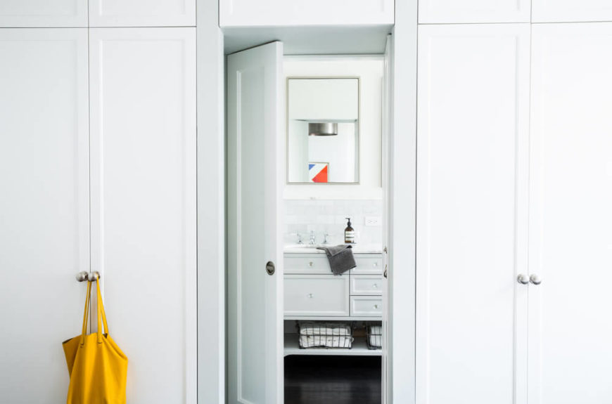 Bookended by full height cabinetry in white, the bathroom entrance opens to reveal pristine white vanity over more of the dark hardwood flooring.