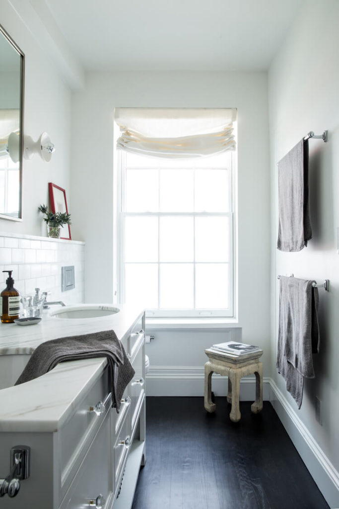 The compact and cozy bathroom boasts more marble atop its traditionally styled dual vanity.