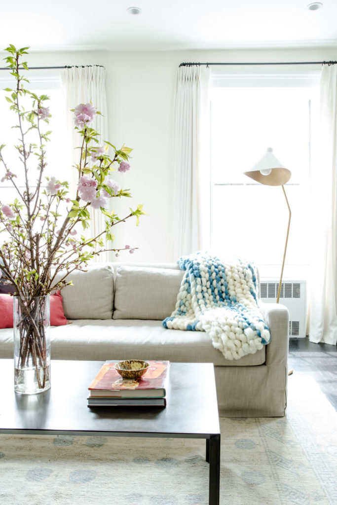 Bright beige sofa and light hued area rug help lighten the space, contrasting with a minimalist, dark coffee table. Modern floor lamp in back adds another idiosyncratic touch.
