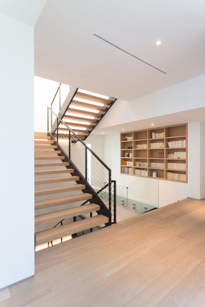 Лестницы в доме открыты-дизайн смеси металла и древесины, по бокам стеклянные панели для максимальной видимости. Тонкий натурального дерева, стеллажи, встроенные в стены.