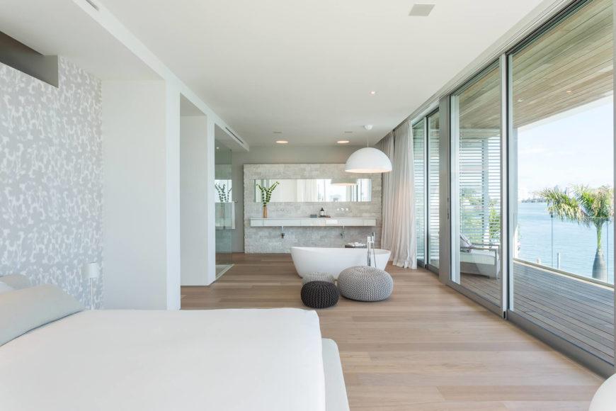 Главная спальня с ванной комнатой-полностью открытое, с тумбой, ванна, стоящих в пространстве между спальней и двойной раковиной. Раздвижные стеклянные панели позволяют отдельным балконом доступа.