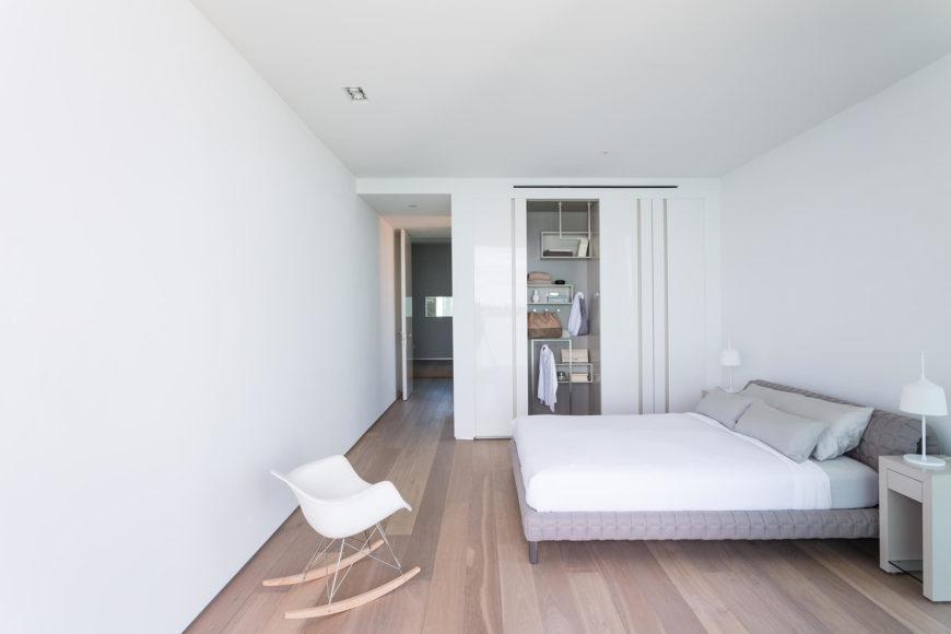 Эта вторичная спальня в девственно-белых над деревянным полом располагает сдержанный и современное решение для хранения на дальней стене.