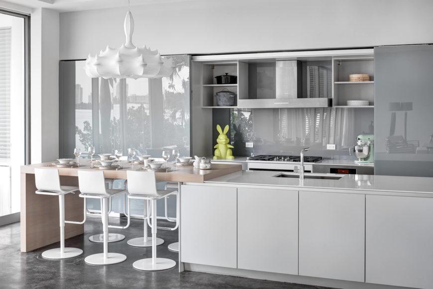 Кухня купается в гладки мебелью и глянцевыми панелями. Большой остров имеет расширение обеденный стол из натурального дерева, с достаточно места для шести человек.