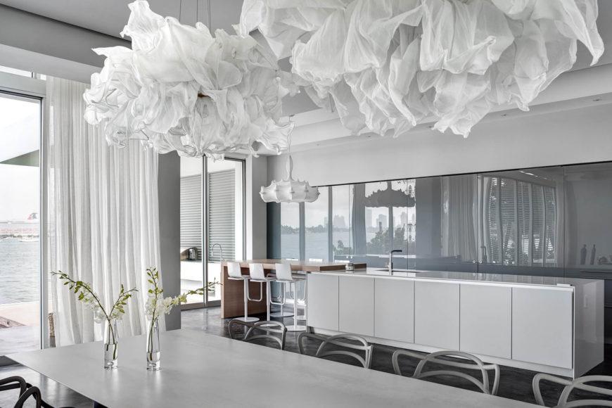 В открытой планировки, столовая делит пространство с кухней. Над обширной таблицы мы видим поразительные скульптурные световые решения.