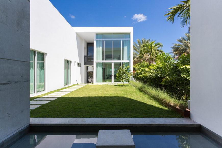 Смотреть Соединительная воды, частный двор-это оазис в пределах этого имущества, заключенного по дому и с густой зеленью.