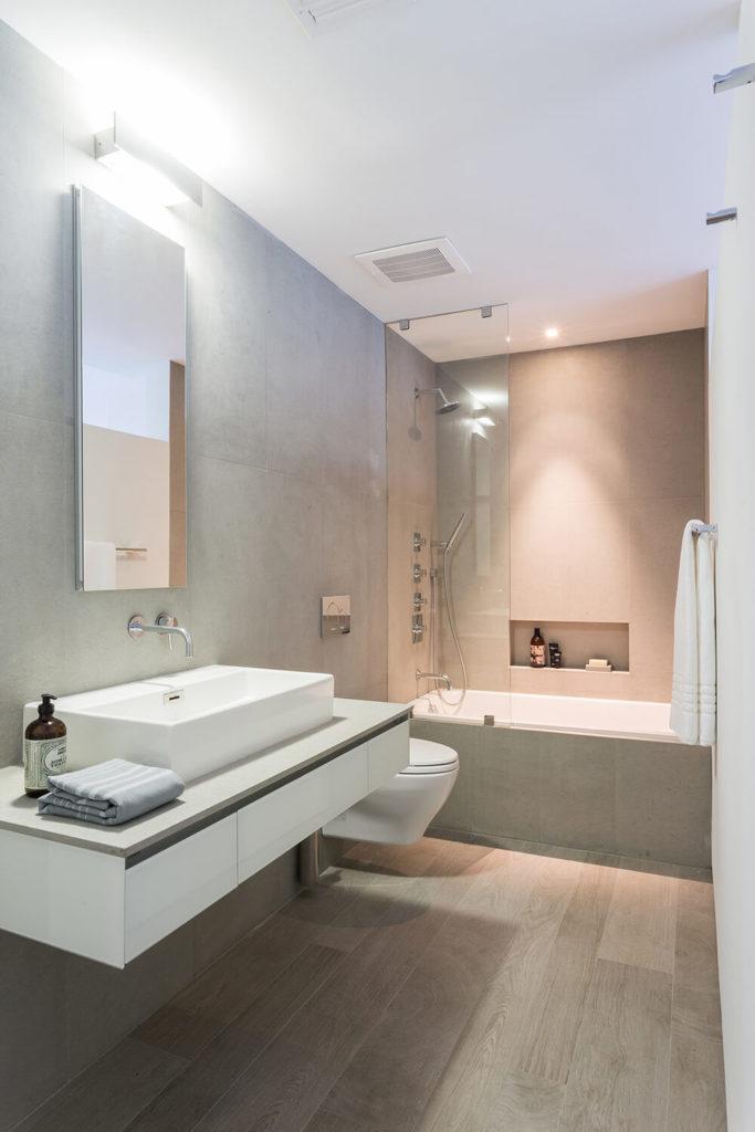 Эта ванная комната дома гладкий с плавающей суета с большой раковиной сосуда. Настенный кран и бескаркасных зеркала дополняют стеклянная душевая кабина для современный вид.