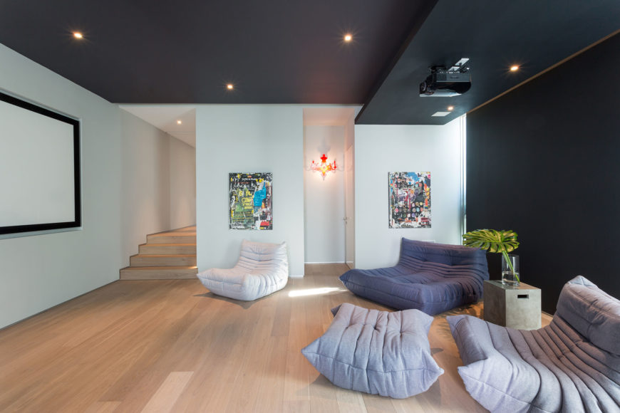 Этот уютный номер СМИ устанавливает ряд современных стульев на пол богатый Деревянный пол, с черной стены и потолок контрастируют с яркой обстановкой.