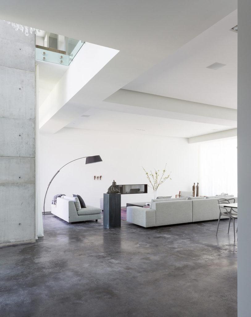 Большой, открытого плана гостиной имеется набор светло-серый современный отборочных на просторах темным каменным полом, контрастируя с ярко-белым пейзажам. На верхнем этаже можно увидеть перевесившись через в левом верхнем углу.
