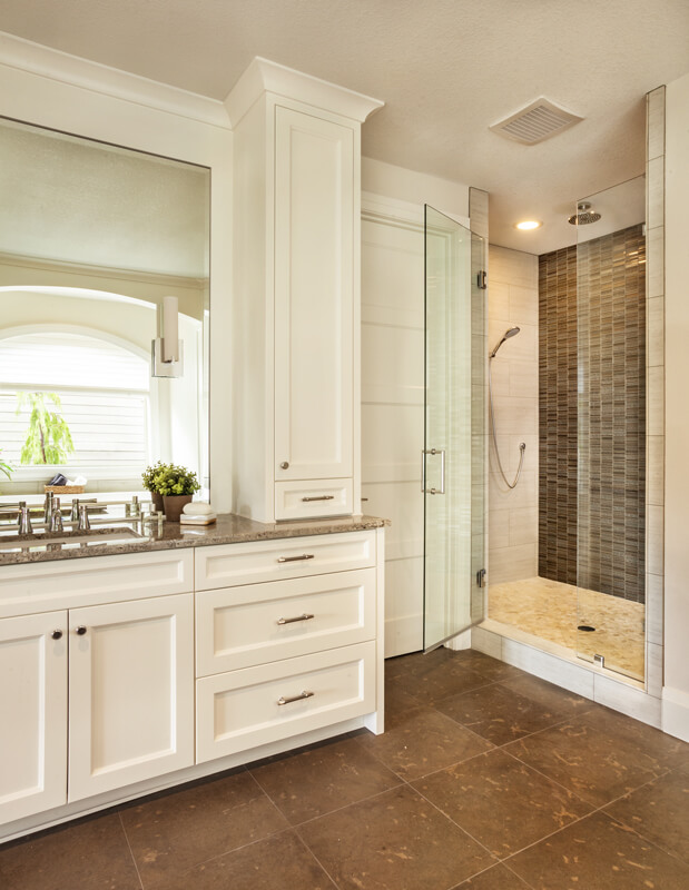 One of the two master bathrooms with custom cabinetry and a walk-in shower in beige and brown tile.