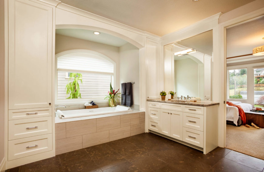 A second master bathroom with a large soaking tub and plenty of storage space. An open archway leads into the master bedroom.