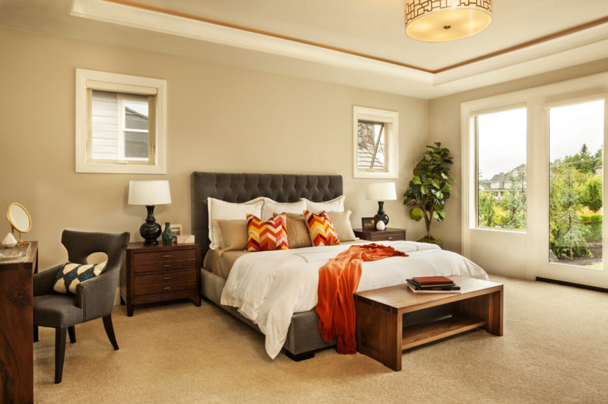 One of the two master bedrooms with an upholstered bed frame, makeup table, and expansive windows.
