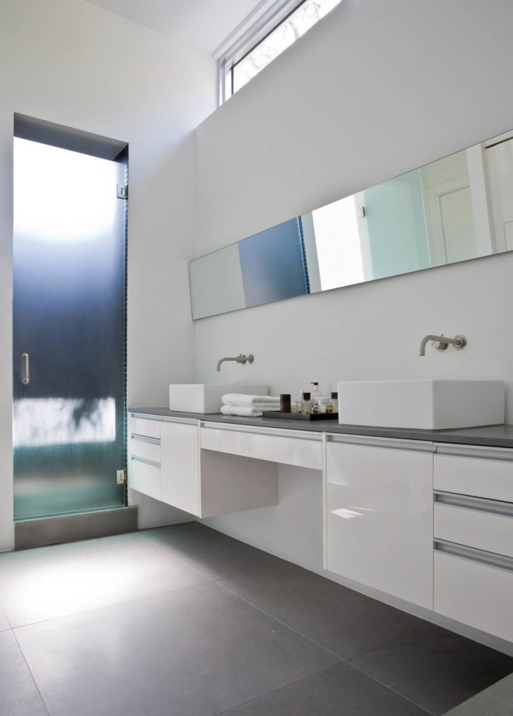 The bathroom displays an unabashed progressive style, with floating dual vanity in glossy white holding a pair of cubic vessel sinks. Wall-mounted faucets and sleek mirror strip enhance the modern appearance.