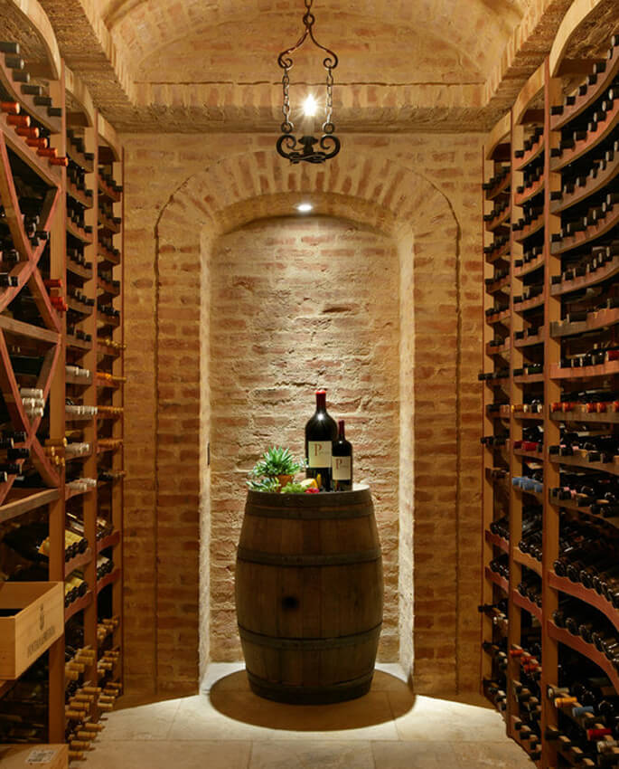 small wine cellar with a barrel tasting table on the far wall. The ...