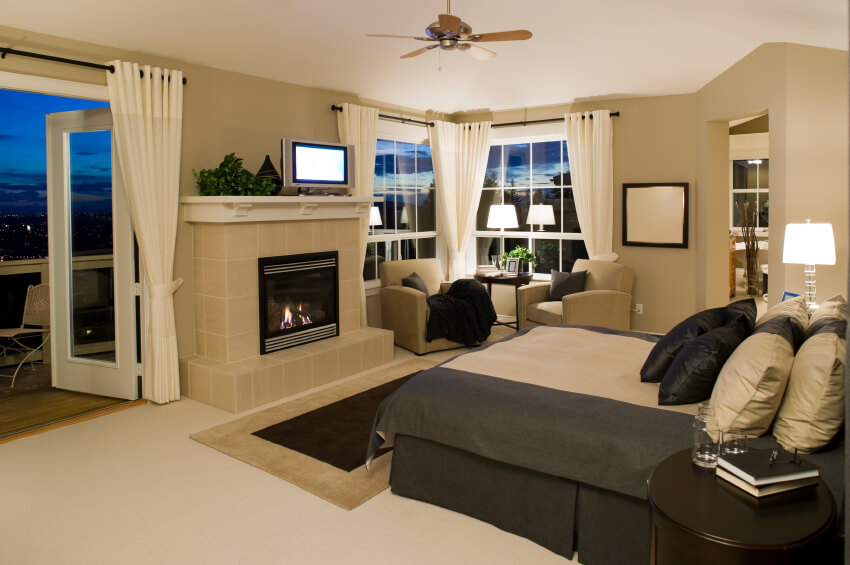 Master Bedroom With French Doors And A Large Stone Fireplace.
