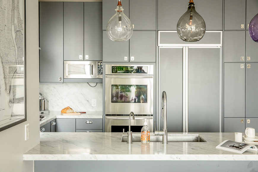 As we look across the kitchen's island, we see the modular cabinetry of all shapes and sizes seemingly built around the stainless steel appliances. The refrigerator is masked by a facade that matches the gray of the cabinetry.