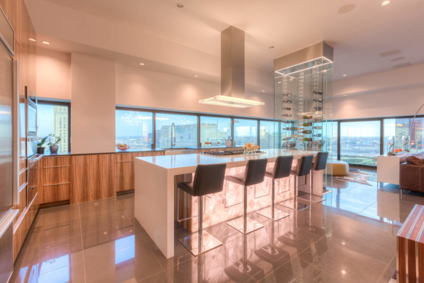 "The kitchen centers on a large, sleek white island with ample barstool seating and a built-in range. Natural wood cabinetry surrounds the island in contrast, with countertops spreading below the immense, nearly full-height windows surrounding. The ""floating"" glass wine rack can be seen towering at right."