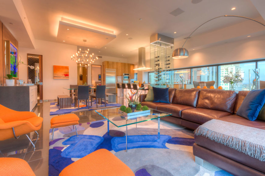 The living room within the open-plan space centers a leather sectional and bright orange lounges over a large multi-colored area rug, with the dining, kitchen, and full window wall in background. Exquisite details abound, including glass coffee table, large format tile flooring, and multiple layers of lighting throughout.