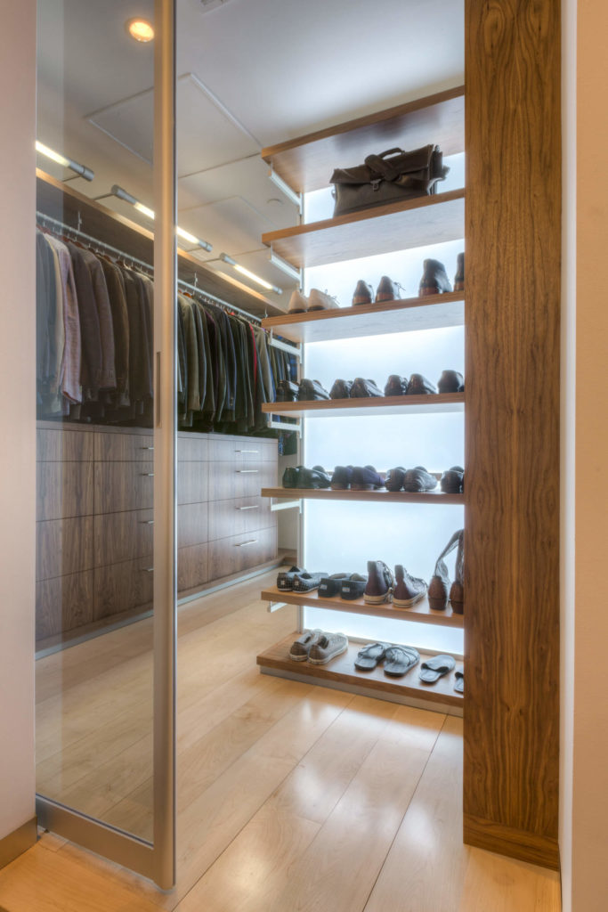 The custom designed walk-in closet is seen behind a glass and metal pocket door, with inner-lit shelving and an array of rich wood drawers and cabinetry making for a sparkling appearance.