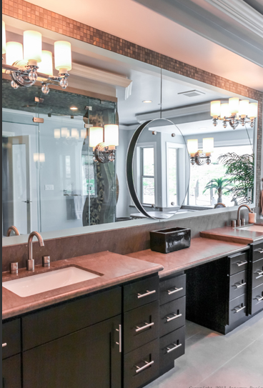 In the master bedroom, some of the unique luxurious touches return. From this angle, we can see the dual vanities with a make-up table between the two. A circular mirror is layered on top of the seamless mirror.