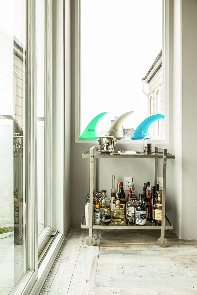 Near the doors to the outdoor patio is a small rolling bar cart that can easily be moved to wherever the party is happening. On the windowsill behind the cart are three surfboard fins.
