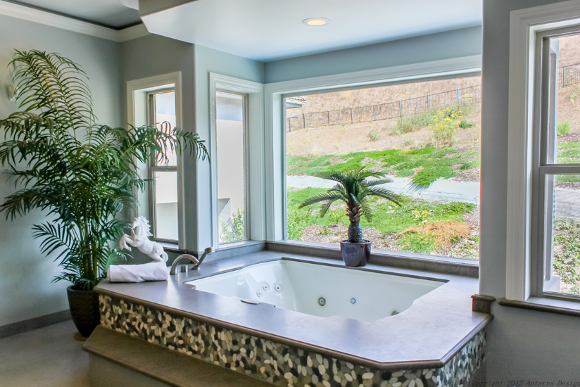 Across from the shower is the large jacuzzi tub settled into the bay windows to the backyard. Small tropical plants help set a relaxing mood.