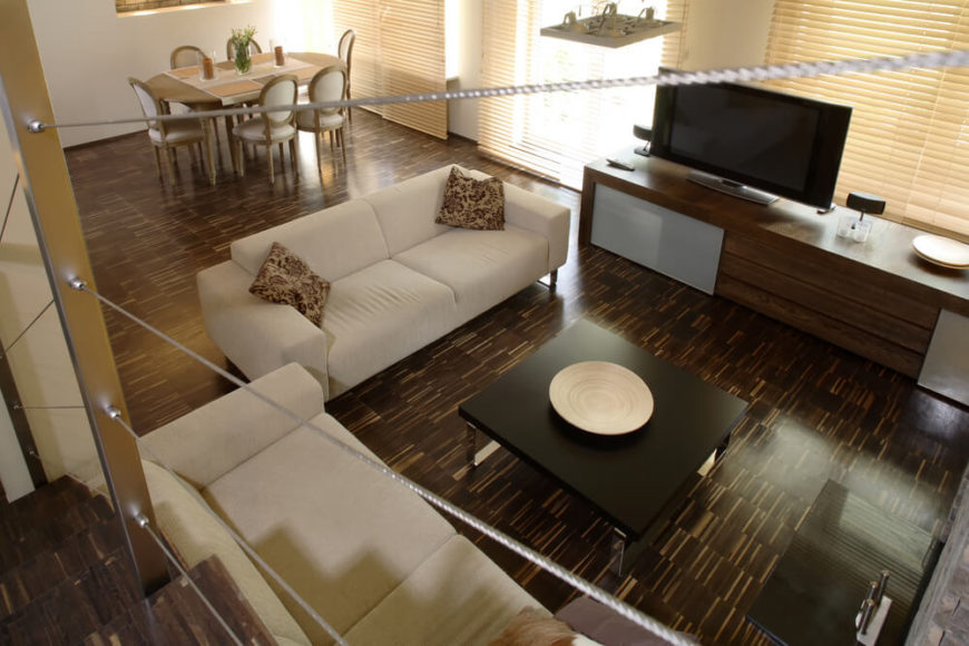 The intense variation of these wood floors mean that they need to be the focal point of the room. Cream sofas and other solids keep all attention on the floor's pattern.