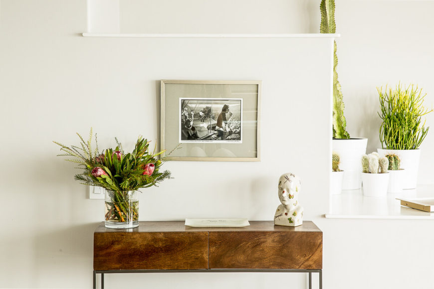 To the left of the entryway is a set of stepped shelving leading down to the dining area. A wooden table topped with a vase, a work of art, and a small bust is combined with a display of cacti on one of the lower stairs just to the right.