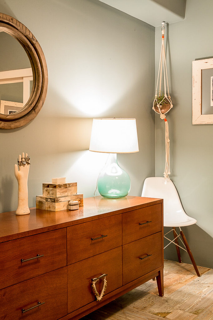 Aside from the closet, other storage is available in the large, richly toned wooden dresser topped with a few small jewelry boxes and a glass lamp.