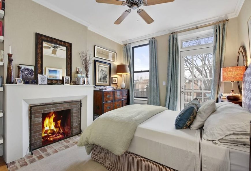 a smaller master bedroom with a brick fireplace and a door leading out onto a deck - Bedroom Ceiling Fans