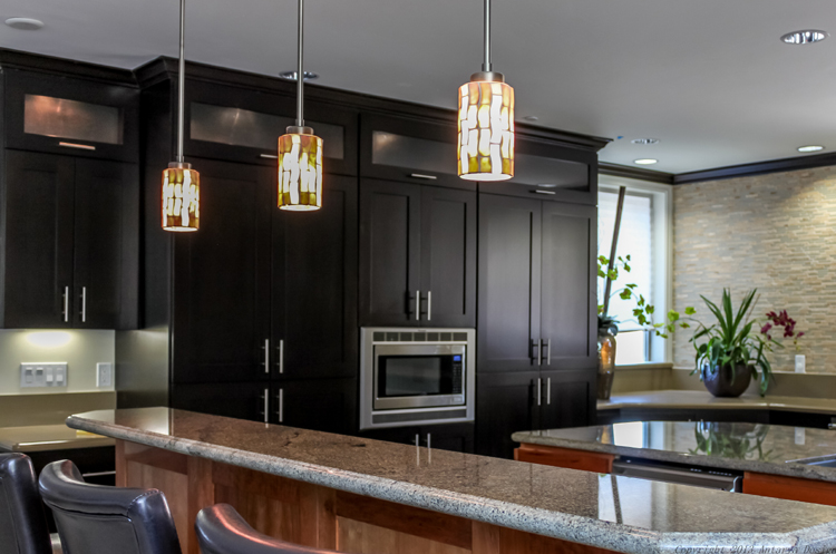 From the eat-in bar, we can better see the frosted glass wall cabinets at the top of the silky black cabinetry. Matching crown molding adds to the traditional feel of this mostly contemporary kitchen.